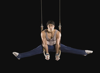 Hispanic male gymnast performing on rings