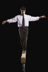 Hispanic businessman walking on balance beam