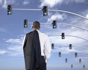 African businessman standing under traffic lights