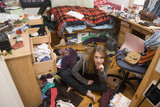 Hispanic teenaged girl sitting in messy bedroom