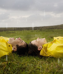 Hispanic couple in rain gear laying on grass
