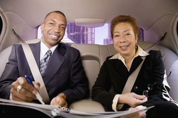 Business people working in back seat of car