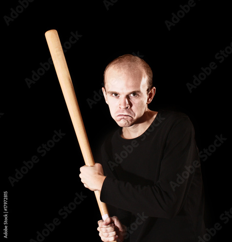 Man with  baseball bat on black background