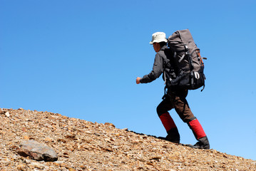 a backpacker walks up laboriously on the macadam slope .