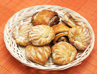 Wicker basket with freshly baked pastries on bamboo mat