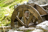 Fototapeta Old watermill with a wooden wheel and stone walls
