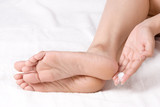 Applying cream to ankle poster