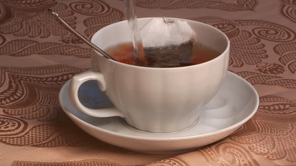 boiled water stream flows in a cup with tea in a bag.