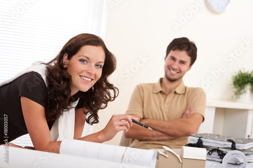 Smiling man and woman with architectural model