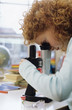 Girl (7-9) using microscope