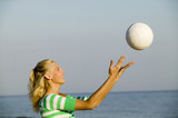 Young woman playing with ball on beach, side view
