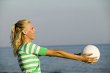Young woman with ball on beach, smiling, side view