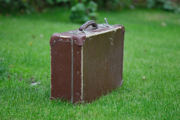 old suitcase on green grass