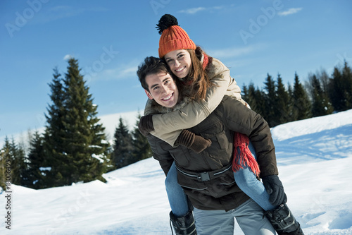 Young woman riding piggyback on young man in winter scene