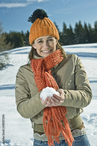 Young woman holding snowball in winter scene