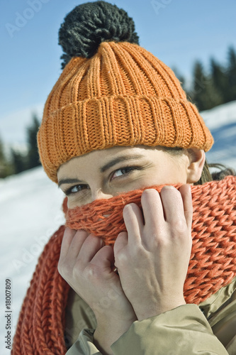 Young woman covering face with scarf in winter scene