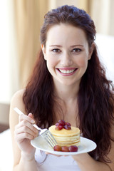 Smiling young brunette eating pancakes with fruit and honey