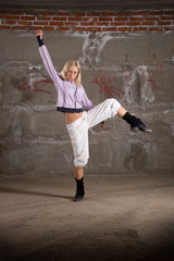 Beautiful hip hop girl dancing over grey brick wall
