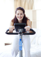 Woman doing spinning bike at home
