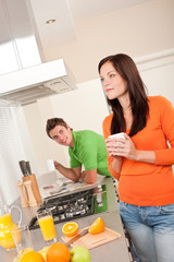 Young woman having coffee in the kitchen