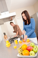 Happy couple preparing food together in the kitchen