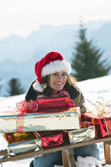 Young woman with Christmas presents in winter scene