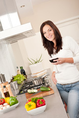 Young woman with glass of red wine in the kitchen