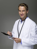 Male Doctor writing on chart, portrait