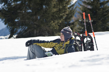 Young man sitting in snow with hiking gear