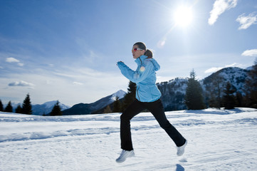 Young woman running in snow