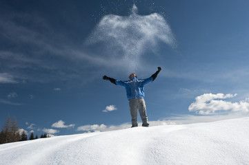 Young man in winter scene with snow spray, arms outstretched
