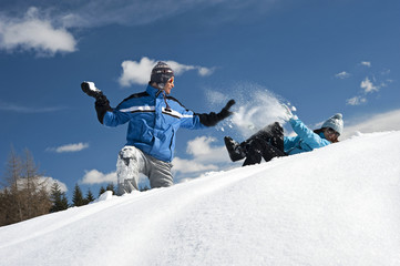 Couple in snow, young man throwing snowball
