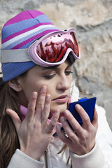 Young woman with wool hat and ski shades checking makeup