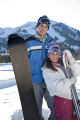 Couple with snowboard and skis