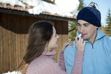 Couple outside of ski lodge, young woman applying lip balm to young man