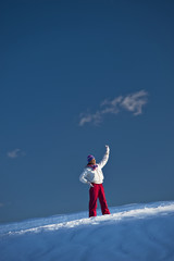 Young woman in snow waving