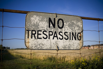 No trespassing sign against backdrop of farmland and houses