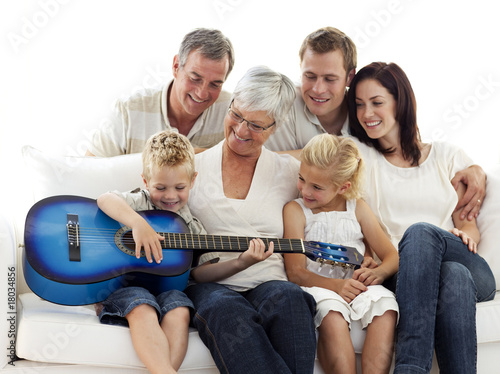 Happy family playing guitar at home