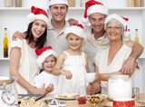 Children baking Christmas cakes in the kitchen with their family