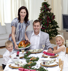 Parents and children celebrating Christmas dinner with turkey