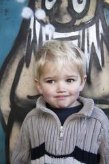 Kleiner Junge vor einem Graffiti