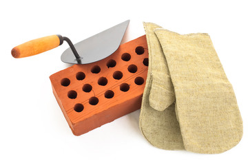 Red perforated ceramic brick, trowel and gauntlet isolated