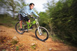A young man riding a mountain bike downhill style