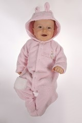 baby boy in pink rabit get-up on gray background