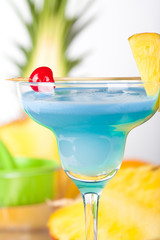 Blue alcohol cocktail with pineapple and cherry