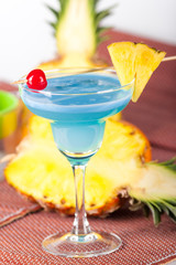 Blue alcohol cocktail with cherry
