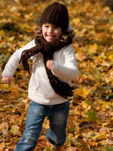 Happy girl running in autumn park