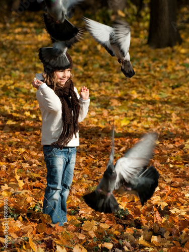 Little girl feeding birds in autumn park