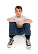 Pre teen boy student sitting in jeans and t-shirt