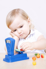 Little girl playing with scale, fruits and vegetables